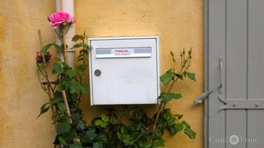 Briefkasten mit Rose an einer Hauswand in Südfrankreich